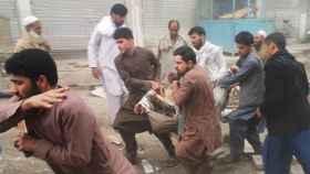 Varias personas evacúan a un herido en un atentado en Kabul.