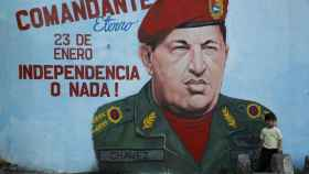 Un niño delante de una pintada de Hugo Chávez en Caracas.