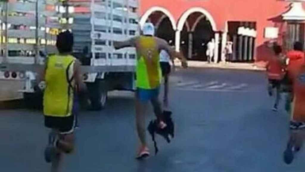 Un corredor le da una patada a un perro.