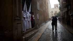 Penitentes de La Candelaria esperan a que pase la lluvia durante la Semana Santa de 2012 en Sevilla, que cayó a primeros de abril.