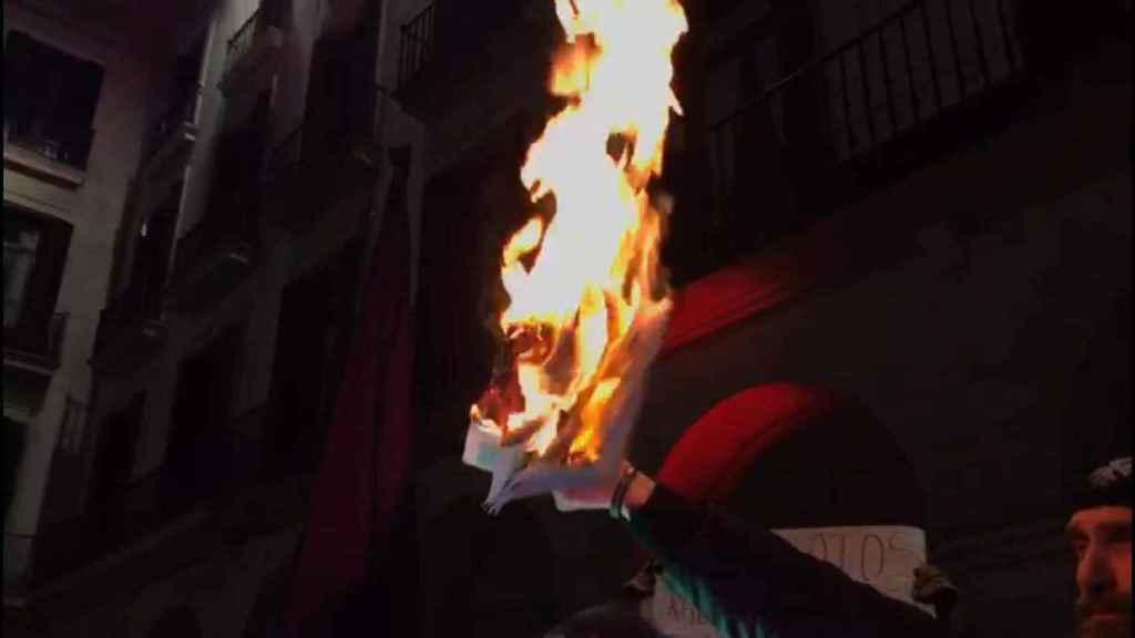 Un policía sostiene una foto ardiendo del SUP en una manifestación de Jusapol