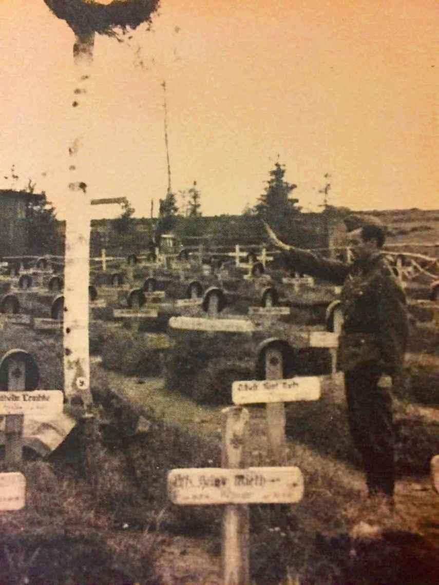 De Gregorio, con el brazo en alto ante la tumba de uno de sus mejores amigos, caído en Rusia.