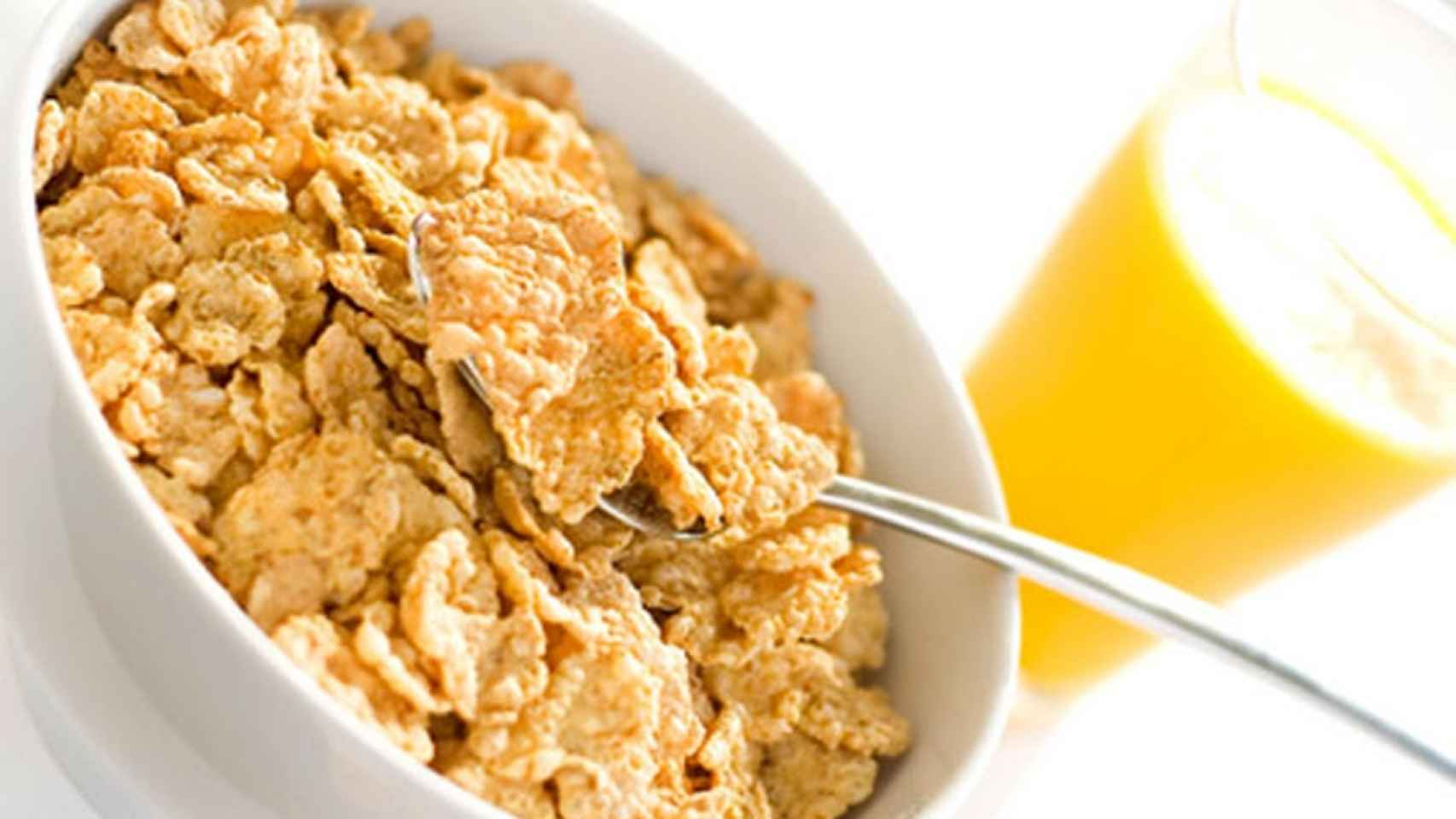 Un tazón lleno de cereales junto a un vaso de zumo.