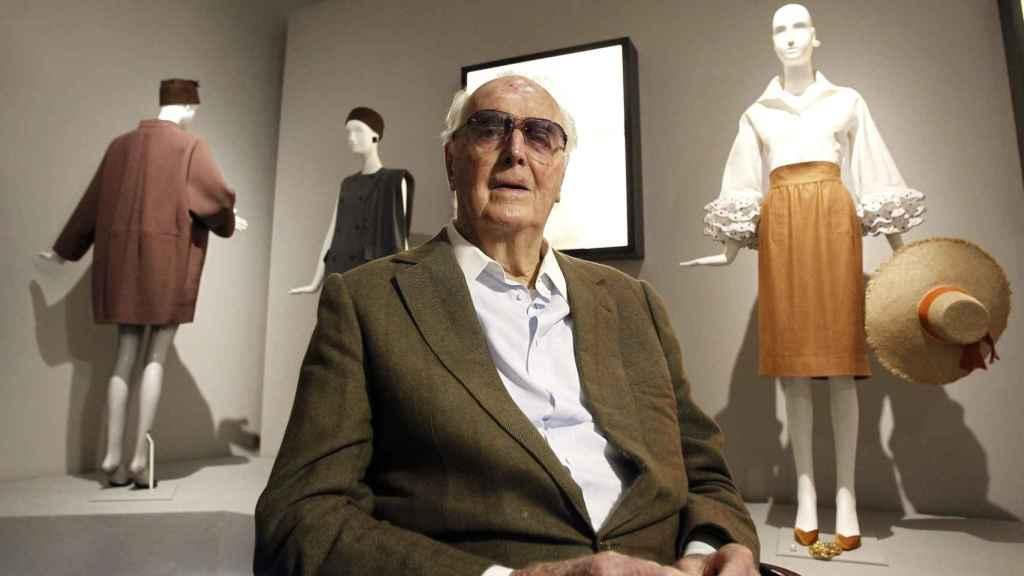 Hubert de Givenchy junto algunos de sus diseños.