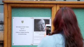 Una estudiante fotografía la necrológica de Stephen Hawking en Cambridge.
