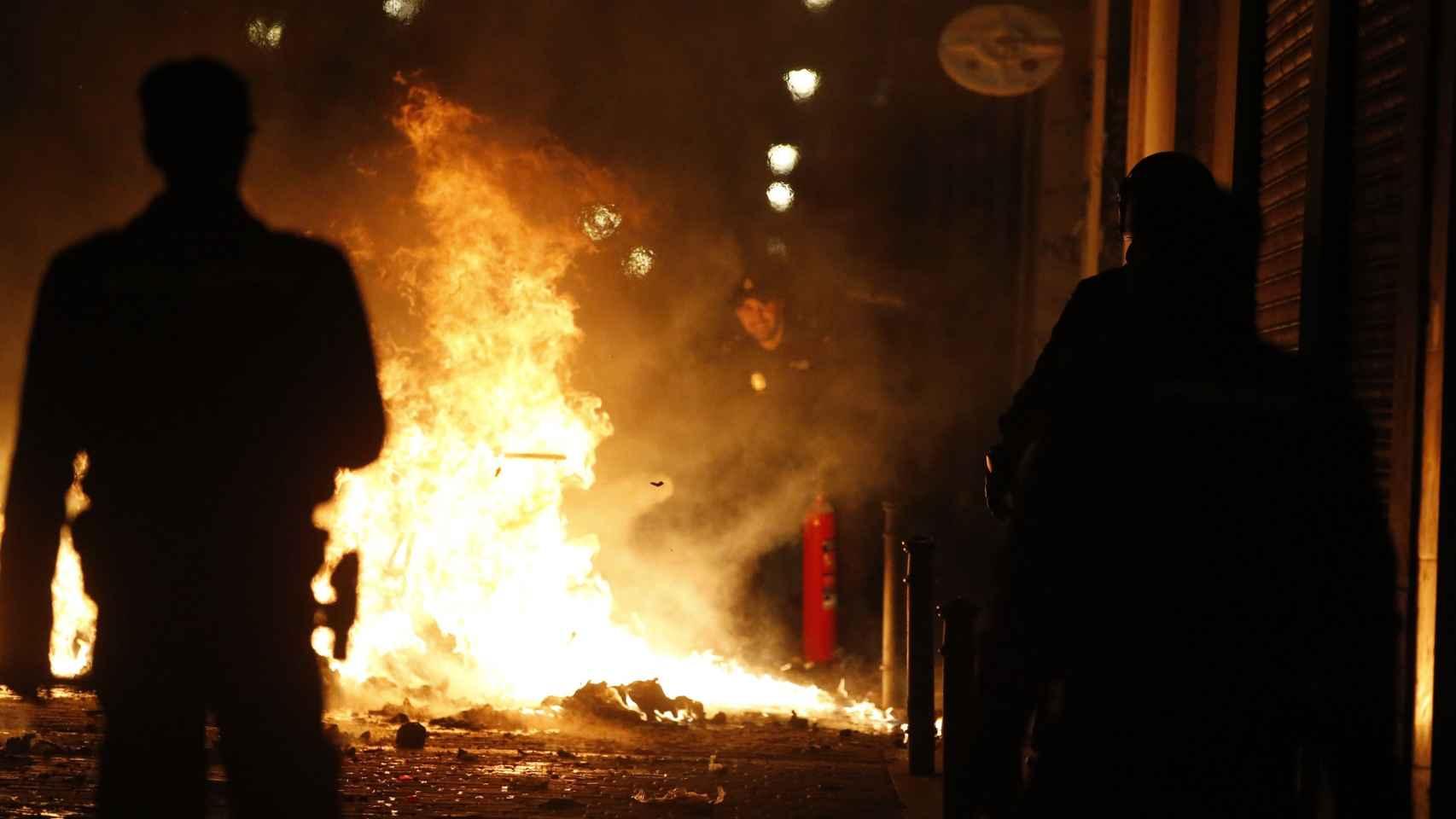 Dos personas presencia los contenedores y la basura quemados en una de las calles del barrio madrileño
