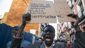 Un manifestante en Lavapiés muestra un cartel de protesta contra el racismo institucional.