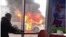 Un ruso disfruta de un café a unos metros de un autobús ardiendo