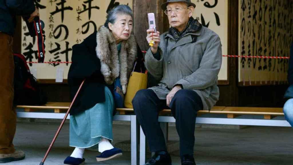 Una pareja japonesa consulta su teléfono móvil.