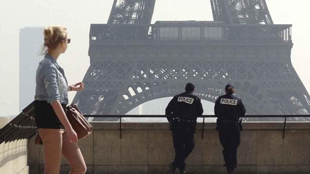 Una turista junto a dos policías en la Torre Eiffel