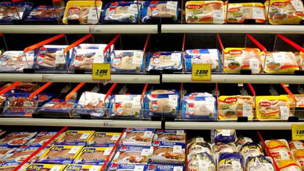 La estantería de un supermercado repleta de bandejas con pollo.