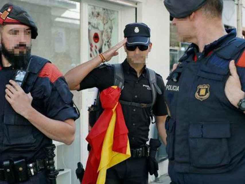 Un policía nacional se despide de los ciudadanos que le aplauden después de ser desalojado de su hotel en la costa catalana.