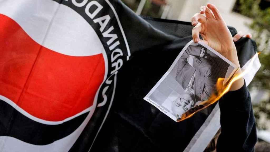 Un manifestante quema una fotografía del juez LLarena