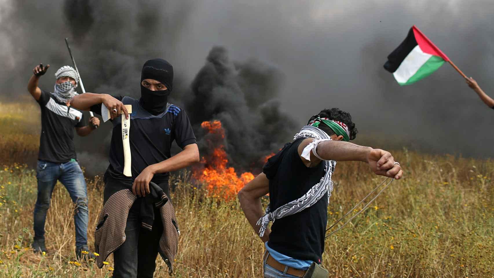 Un manifestante palestino sostiene un hacha durante los enfrentamientos con las tropas israelíes.