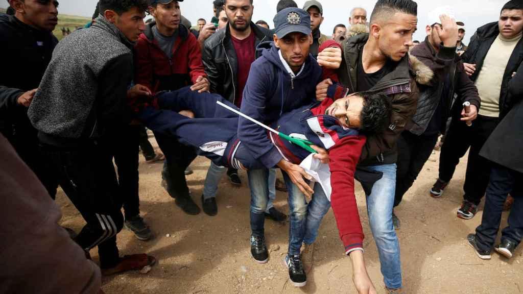 Varios palestinos transportan a un herido por el choque con el ejército israelí.