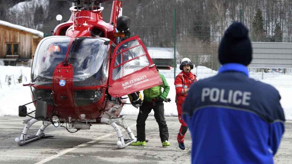 Un policía observa el aterrizaje del helicóptero de Air Zermatt tras la búsqueda en la zona donde se produjo el alud, en Valais.