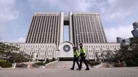 Varios policías patrullan el exterior del Tribunal del Distrito Central de Seúl, previo a la audiencia de sentencia para la expresidentaPark Geun-hye.