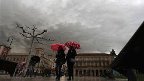 Dos chicas pasean bajo un paraguas el pasado mes de abril en Pamplona.