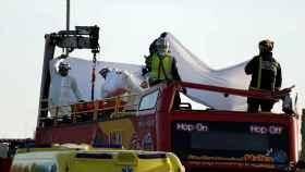 Los servicios de emergencia retiran un cadáver del autobús.