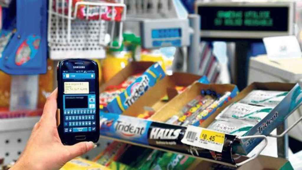 Un cliente con un móvil en un supermercado, en una imagen de archivo.