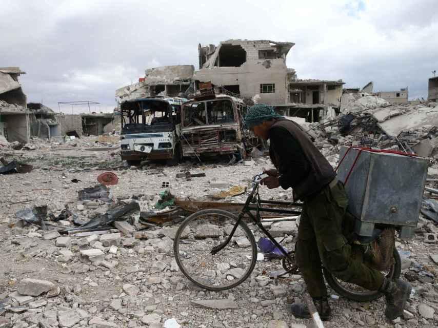 Un hombre camina con su bicicleta entre los escombros de Duma, en Siria.