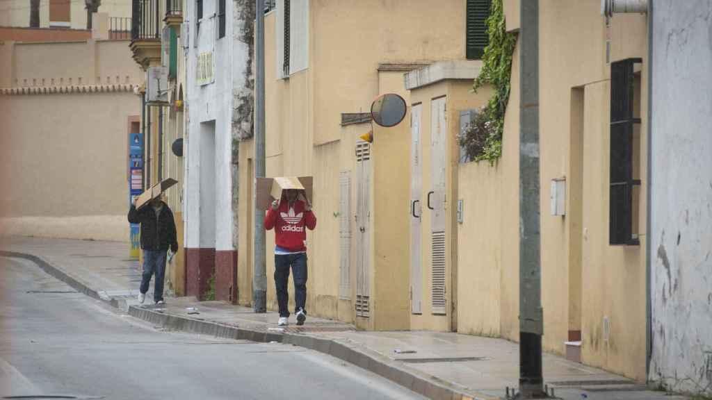 Agustín (sudadera roja) y su compañero caminan bajo un fuerte aguacero por las calles de Sanlúcar de Barrameda este pasado martes.