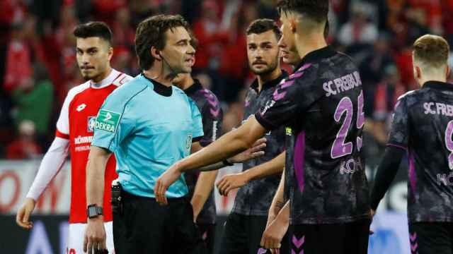El árbitro les explica la decisión a los jugadores del Friburgo.