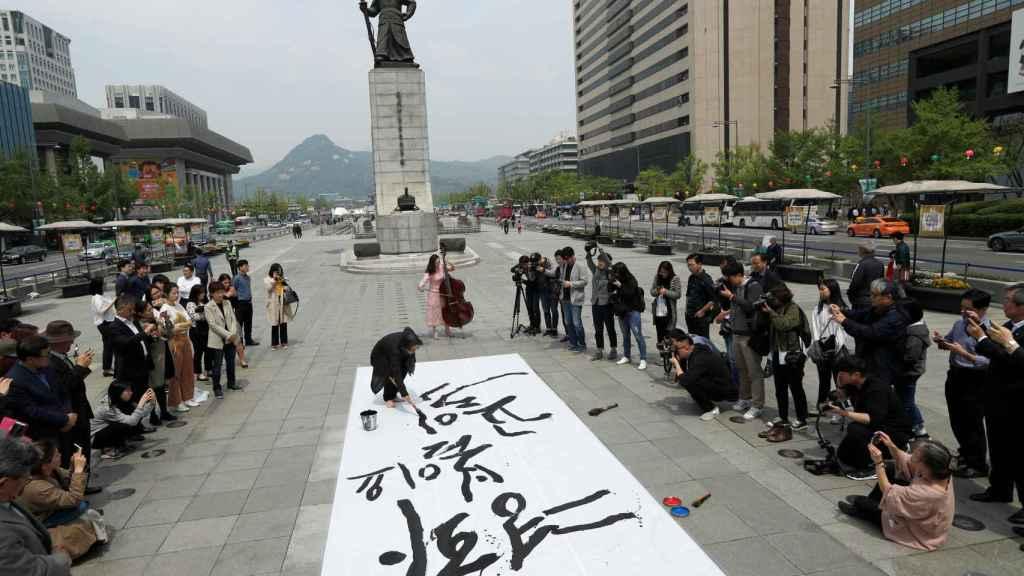 Un artista surcoreano realiza un pintura durante un acto a favor de la unificación entre las dos Coreas.