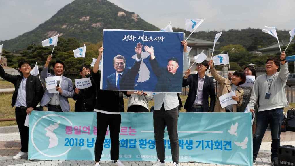 Un grupo de estudiantes sostiene dos carteles de Kim Jong-un y Moon Jae-in.