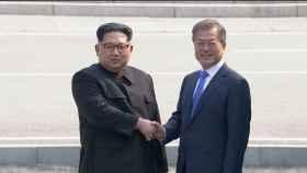 Kim Jong-un (i),estrecha la mano del presidente de Corea del Sur,  Moon Jae-in (d).