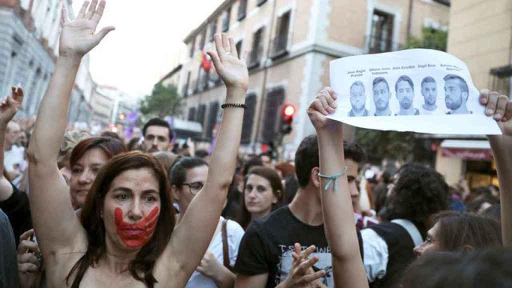 Una mujer con una marca de una mano en la cara levanta los brazos. / Reuters