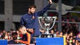 Gerard Piqué, junto al trofeo de LIga, en el bus del Barcelona.