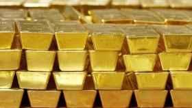 Varios lingotes de oro apilados en un depósito.