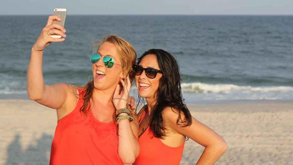 Dos jóvenes se hacen un selfie sonriendo a la cámara.