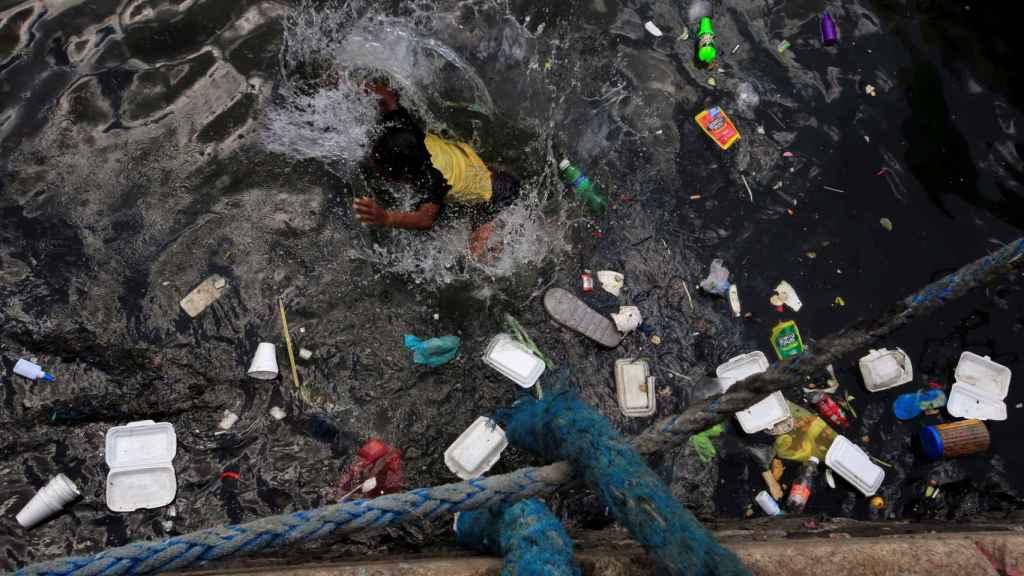 Envases de plástico desperdiciados en el agua en la que nadan los niños del suburbio de Baseco, en Manila, Filipinas.