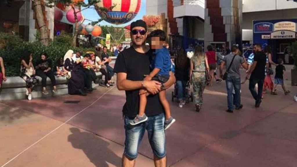 Con su hijo en brazos en un parque de atracciones.