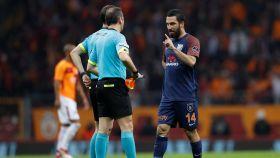 Turan habla con un árbitro durante un partido.