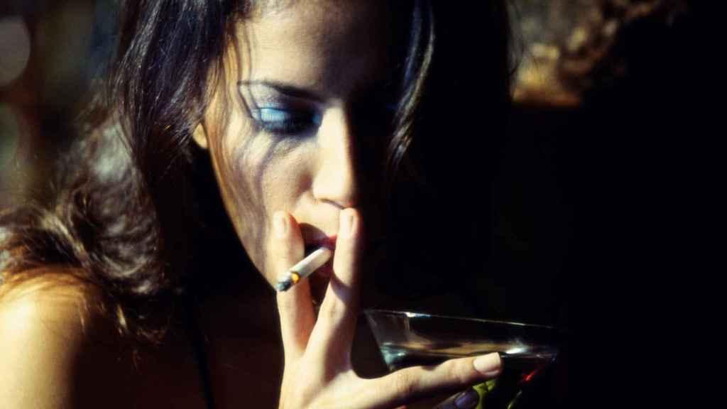 Una mujer fuma a la misma vez que sostiene una copa en su mano.