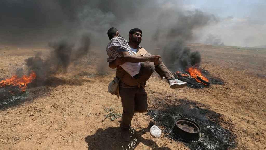Un hombre carga con uno de los heridos en la frontera de Gaza.