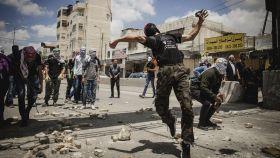 Un grupo de manifestantes palestinos lanza piedras durante los enfrentamientos.