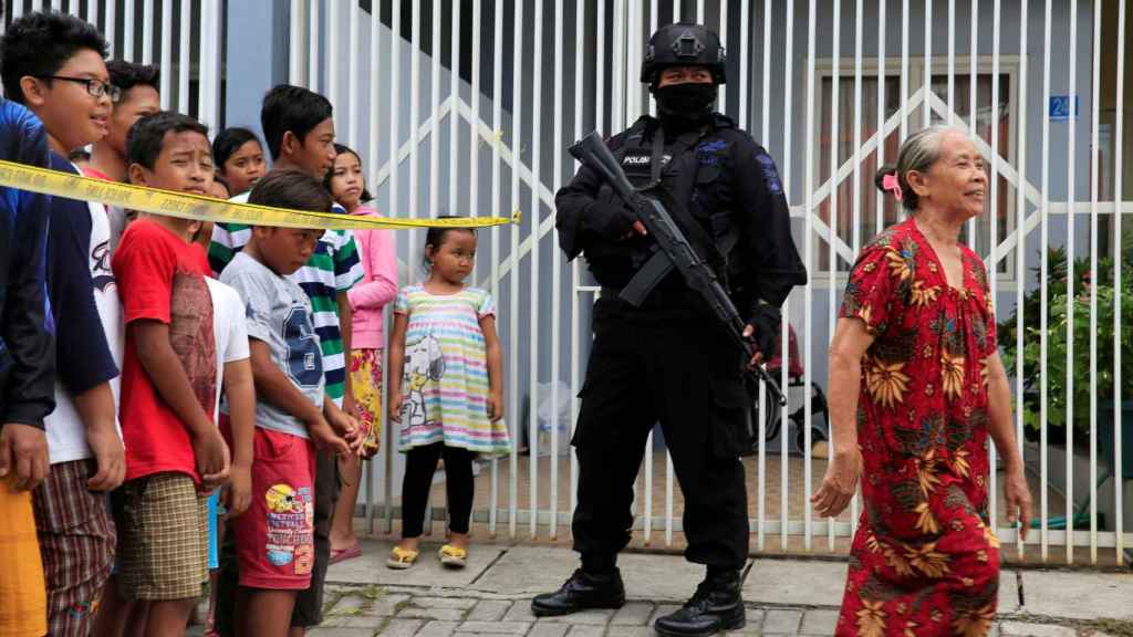 Un agente antiterrorista hace guardia frente a la casa de un presunto terrorista.