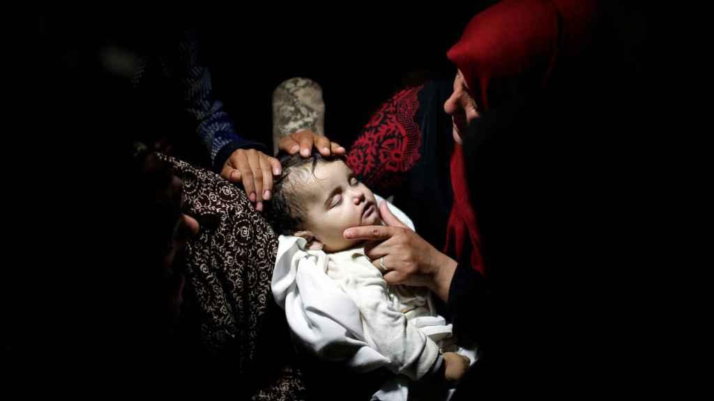 Una madre junto al bebé de 18 meses muerto en Gaza.