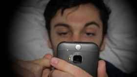 Un hombre consulta el móvil en su cama por la noche.