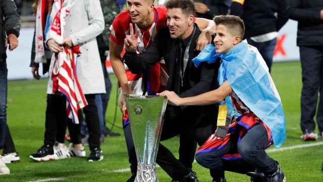 Simeone posa junto a la Europa League con su familia.
