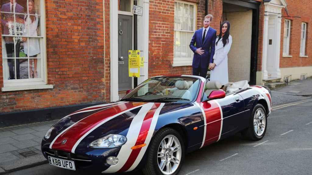 Un jaguar se pasea por la ciudad londinense con dos figuras de Harry y Meghan.