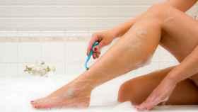 Una mujer se afeita las piernas con una cuchilla.