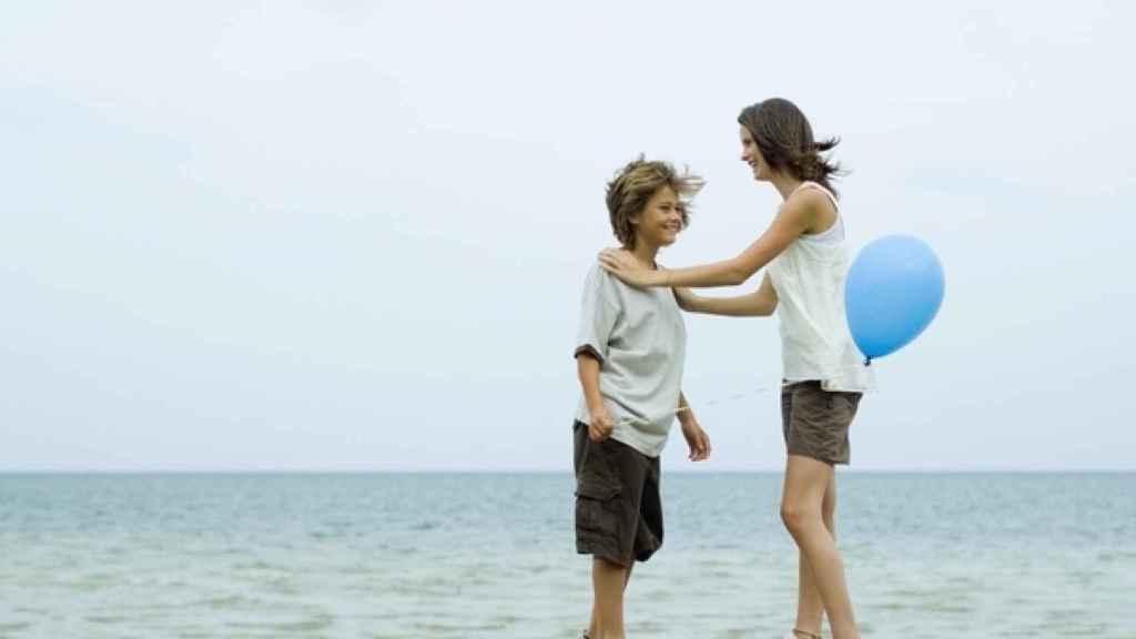 Dos hermanos juegan con un globo de plástico frente al mar.