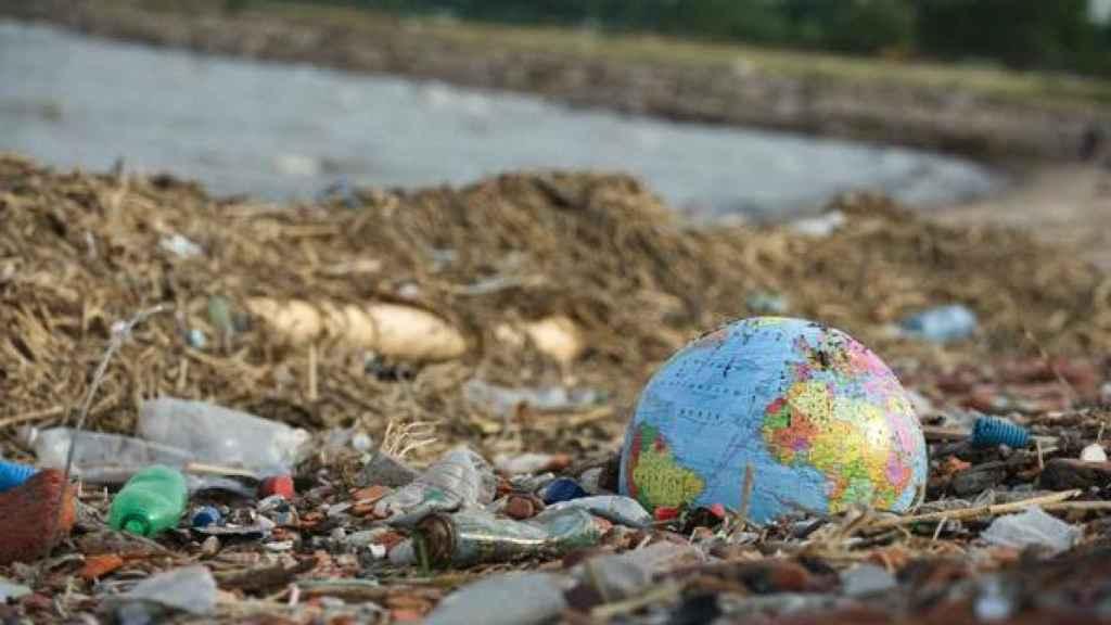 Un globo terráqueo de plástico abandonado junto a los desperdicios en la costa.