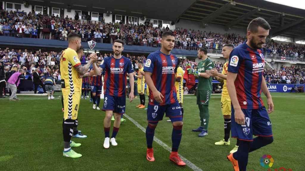 Los jugadores del Huesca le hacen el pasillo a los del Nastic.
