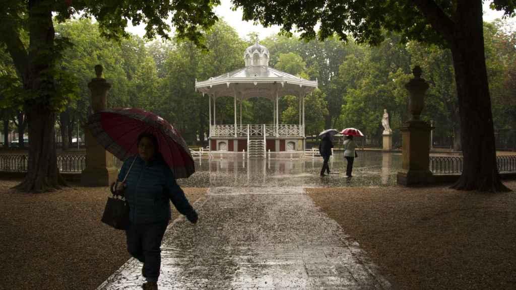 Paseantes se protegen de la lluvia en el parque de la Florida de Vitoria (archivo).